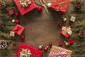 cajas de regalo brillantes con mesa de ramas verdes foto