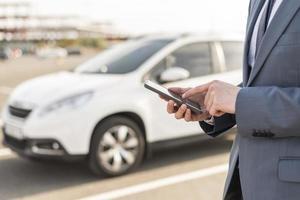hombre de negocios, con, smartphone, delante de, coche foto