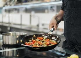 Chef con delantal plato de cocina en la cocina foto