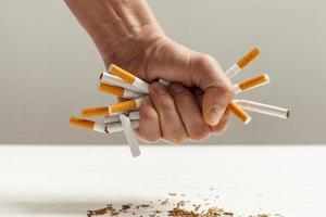 Cigarrillo roto en la mano sobre fondo blanco. foto