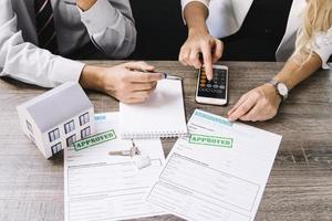 agente cliente calculando el precio de la vivienda foto