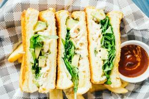Sandwich with avocado and chicken meat with french fries photo