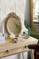 Arreglo con espejo y perfume en mesa de madera. foto