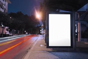 Parada de autobús cartelera en blanco noche con luces coches pasando foto