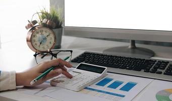 Hand using a calculator near a computer mock-up photo