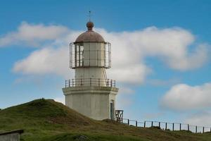 Lighthouse at Cape Pospelova with a cloudy blue sky in Nakhodka, Russia photo