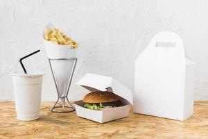 Hamburguesa y papas fritas en vaso desechable sobre mesa de madera foto