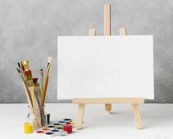 Canvas easel glass filled with paint brushes photo