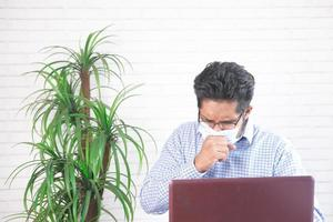 Man wearing mask while coughing at desk photo