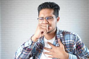 Man coughing into hand photo