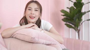 femme asiatique souriante sur un canapé rose video