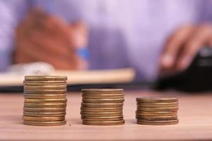 pila de monedas con una persona en el fondo foto