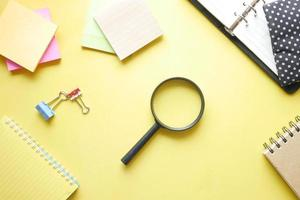 Magnifying glass on yellow background photo