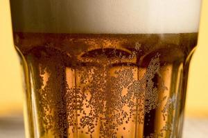 Close-up glass of cold beer with golden bubbles photo
