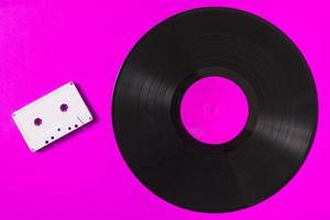 White audio cassette tape and vinyl record on pink background photo