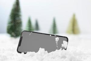 Close-up view of smartphone in snow photo