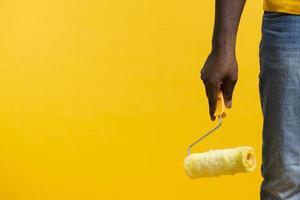 Copie el espacio hombre sujetando la herramienta de pintura sobre fondo amarillo foto