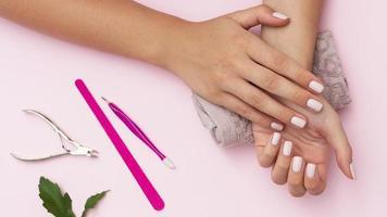 Manos con manicura y herramientas para el cuidado de las uñas sobre fondo rosa foto