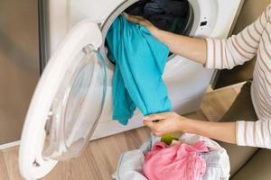 Manos sacando la ropa de la lavadora foto