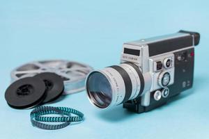 Rollos de película y tiras de película con videocámara vintage sobre fondo azul. foto