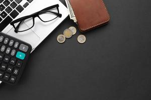 Flat lay wallet near laptop with coins photo