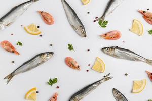 Arrangement of fish and shrimps with lemon on white background photo
