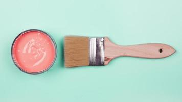 An elevated view of coral paint and bucket with paintbrush on mint background photo