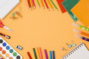 Disposición de útiles escolares enmarcados sobre fondo naranja foto