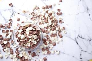 Vista superior de copos de maíz de chocolate en un recipiente sobre un fondo de mármol foto