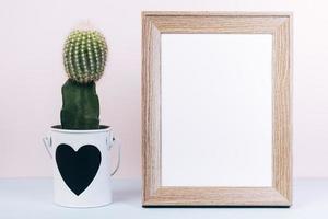 marco de fotos en blanco con planta suculenta y maceta en forma de corazón