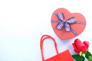 Top view of a heart-shaped gift box and rose on a white background photo
