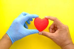 Man's hand in protective gloves holding red heart on yellow background photo