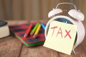 Nota adhesiva de impuestos en un reloj despertador foto