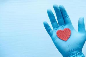 Red heart in gloved hand photo