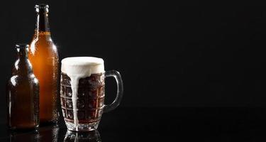 Surtido con sabrosa cerveza sobre fondo negro foto