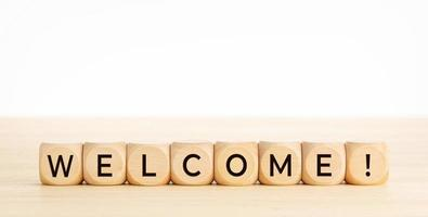 WELCOME word on wooden blocks on wood table photo