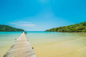 Wooden pier or bridge with tropical beach and sea in paradise island photo