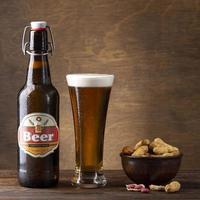 Cerveza y maní sobre fondo de madera foto
