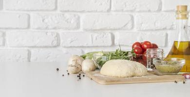 Pizza dough, olive oil, and other ingredients on white kitchen background photo