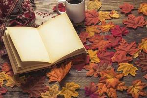 libro en blanco cerca de café y hojas de otoño foto