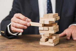 Businessman playing wooden block game, concept photo