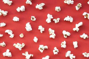 Cinema concept with popcorn on red background photo