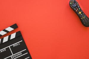 Clapperboard and remote control on red copyspace background photo