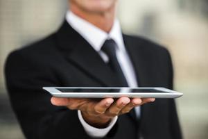 primer plano, hombre de negocios, tenencia, tableta, en mano foto