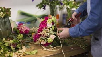 Close-up male florist creating flower bouquet in flower shop photo