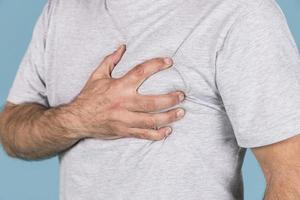 Close-up man's hand holding his heart in pain photo