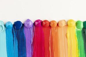 Estelas de pintura de colores sobre fondo blanco. foto