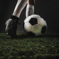 Recortar las piernas pateando un balón de fútbol sobre el césped foto