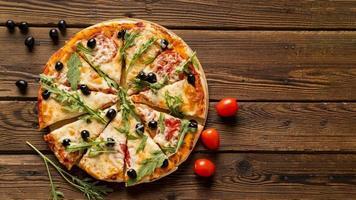 deliciosa pizza italiana en la mesa de madera foto