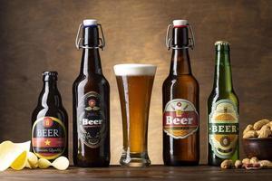 cerveza en diferentes tipos de botellas con bocadillos. foto